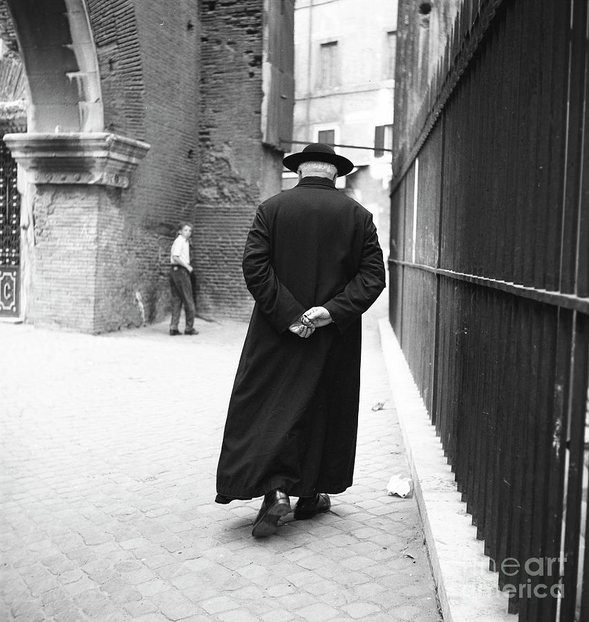 Rome Photograph - A priest walks down a street in Rome, 1955 by The Harrington Collection