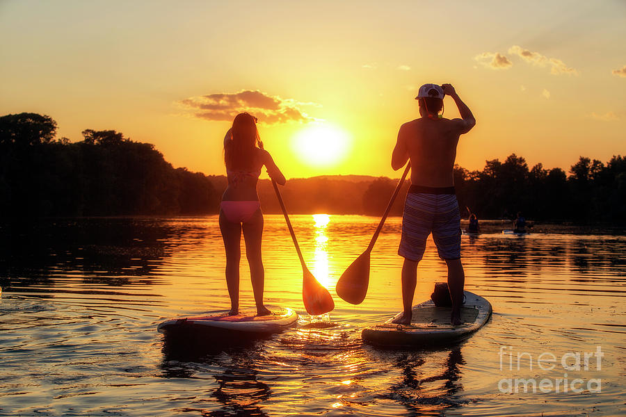 Silhouette Photograph - A silhouette of a couple on a stand-up paddle boards SUP at sunset on Lady Bird Lake in Austin Texas by Austin Welcome Center