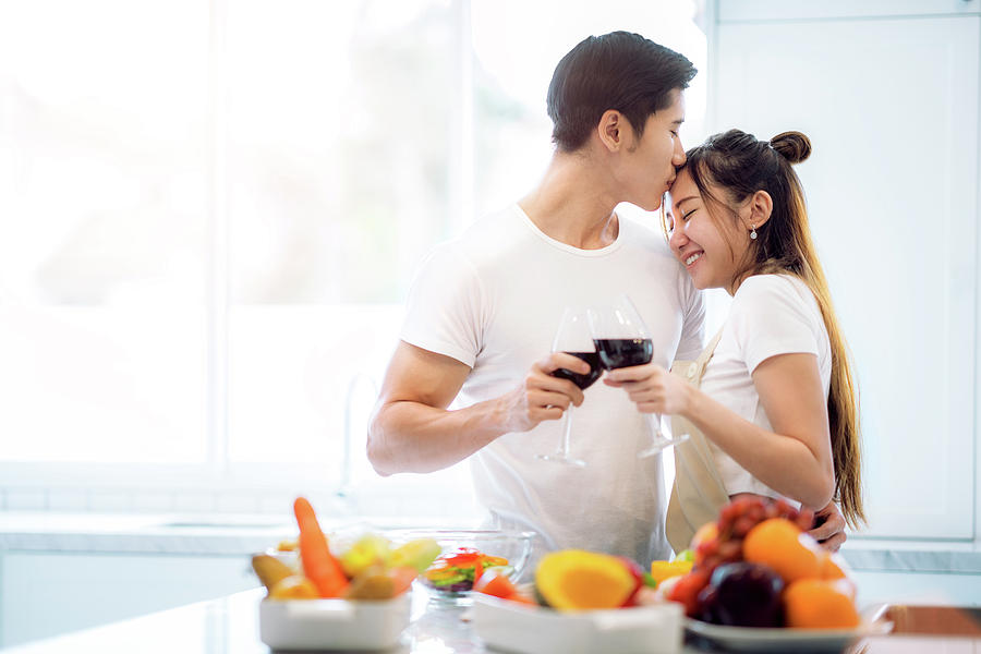 Young Photograph - Asian couple kiss in kitchen by Anek Suwannaphoom