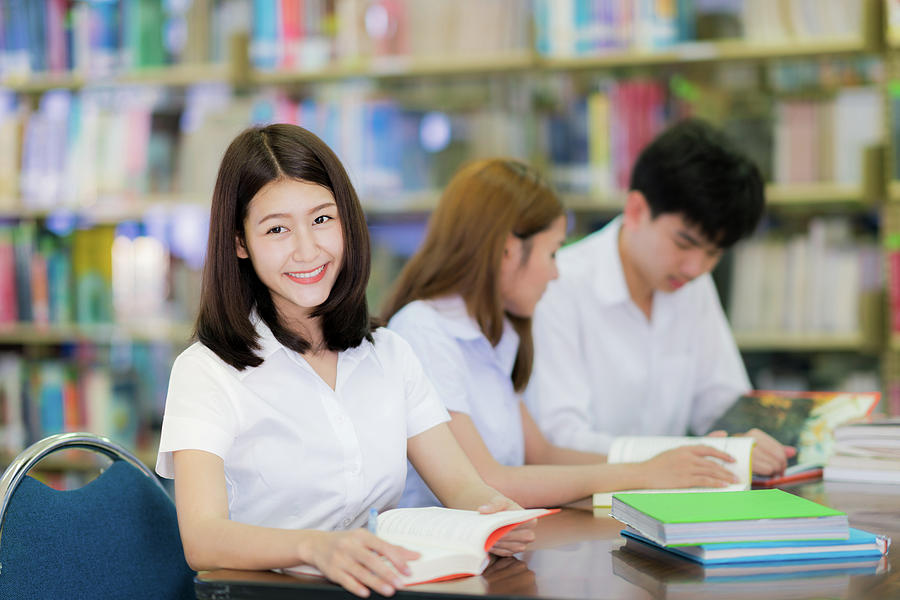 Asian student lady smile and read a book in library in universit ...