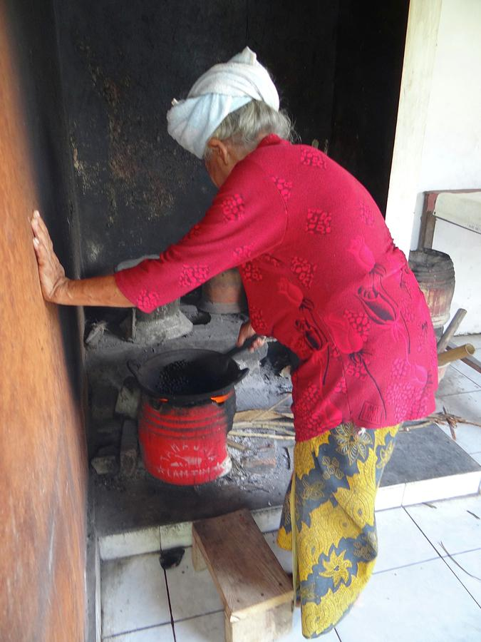 Unschooling Photograph - Balinese Lady Roasting Coffee Leans Again Wall by Exploramum Exploramum