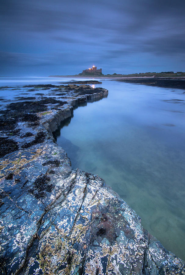 Bamburgh Castle blue hour from the rocks after dark by Anita Nicholson