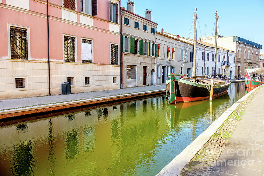 Architecture Photograph - boat in a canal of the colorful italian village of Comacchio in  by Luca Lorenzelli