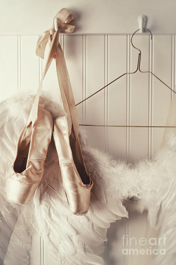 Close up of angel wings and ballet slippers hanging on coat hook by Sandra Cunningham