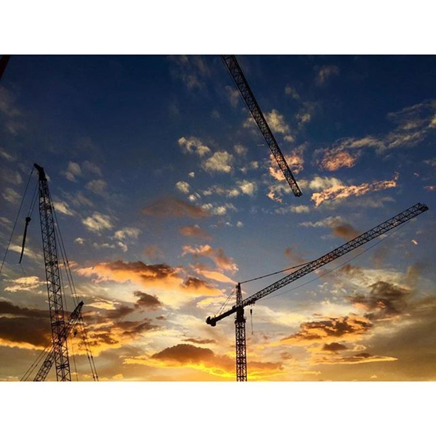 Clouds Photograph - Construction Cranes At Sunset by Juan Silva