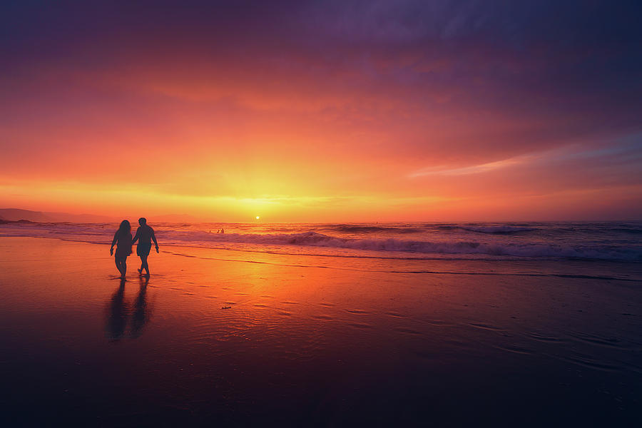 couple walking on beach at sunset by Mikel Martinez de Osaba