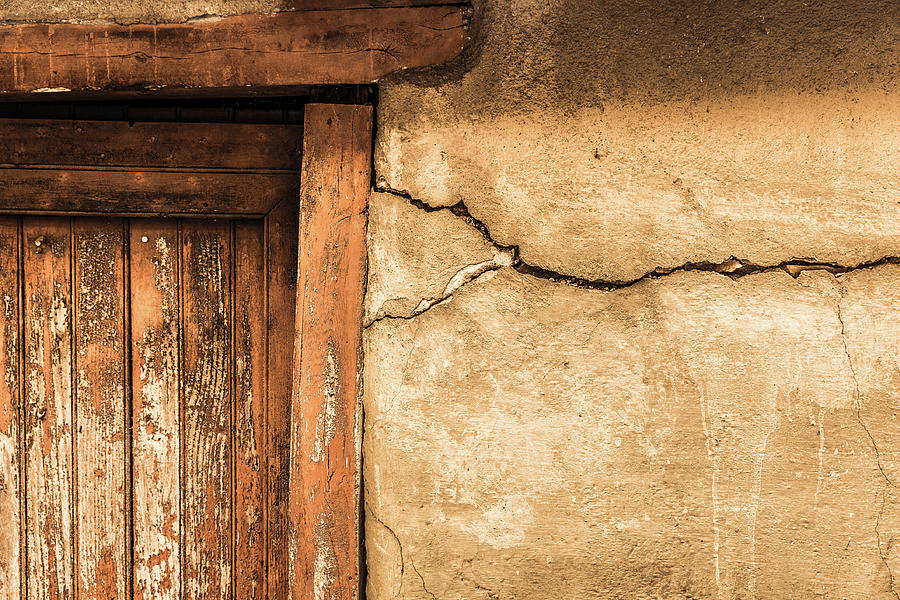 Cracked lime stone wall and detail of an old wooden door by Semmick Photo