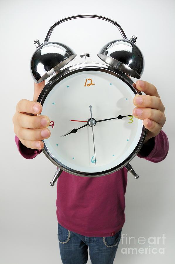Design Photograph - Girl Holding Alarm Clock Over Face by Sami Sarkis