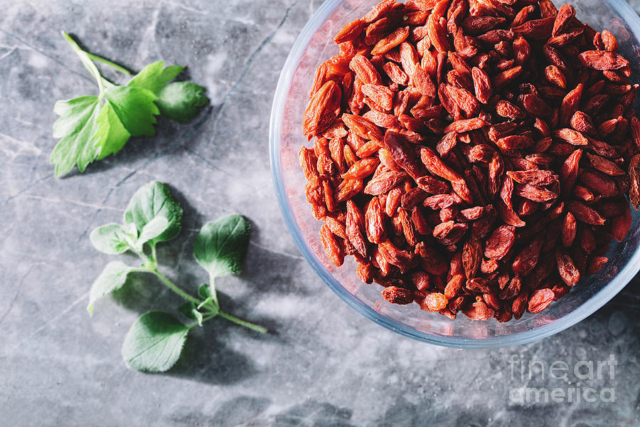 Goji Berries In Glass Bowl Two Green Leaves Nearby Photograph By