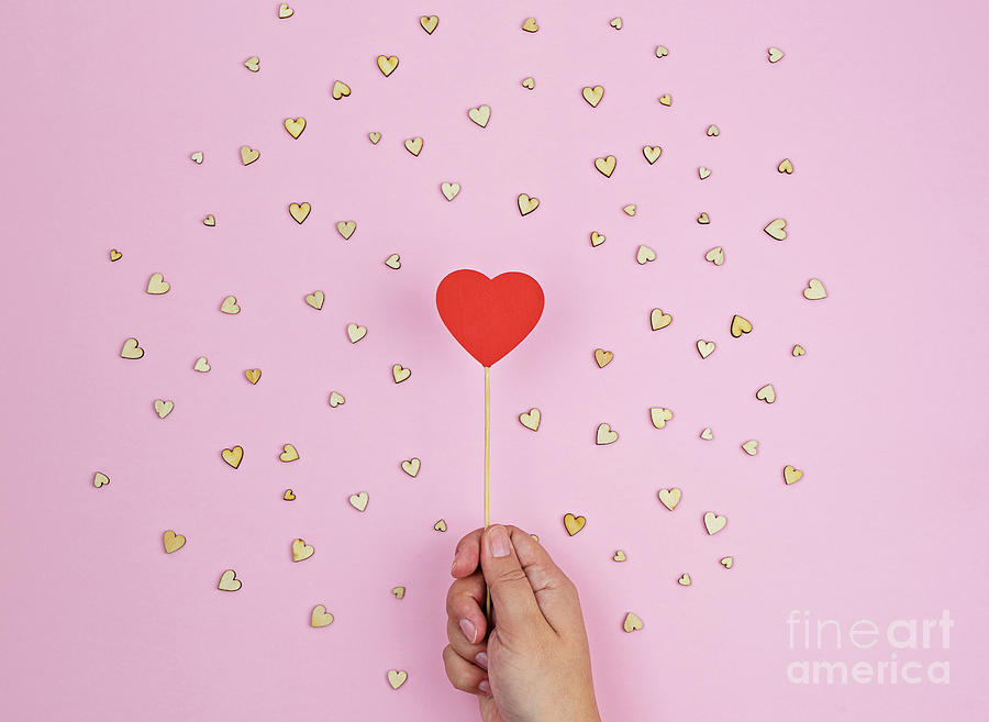 Hand Holds Large Red Wooden Heart On Pink Background Photograph