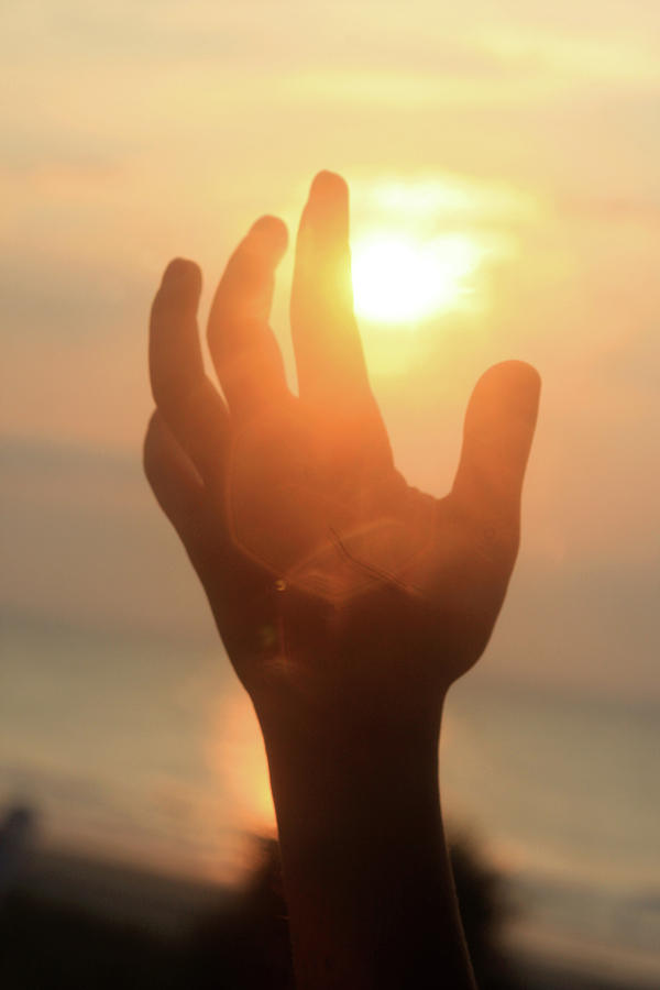 Hand reaching fore the sun by Emanuel Tanjala