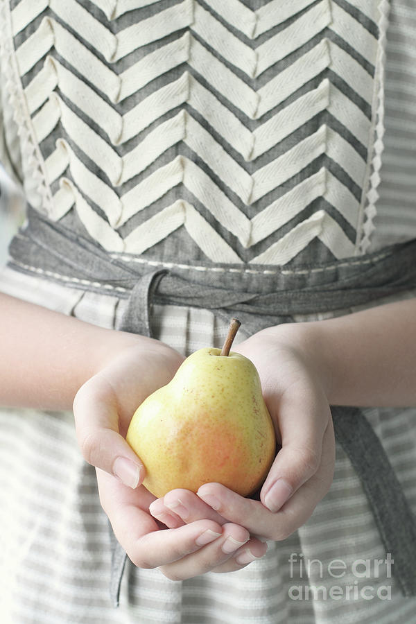 Hands holding yellow pear by Stephanie Frey
