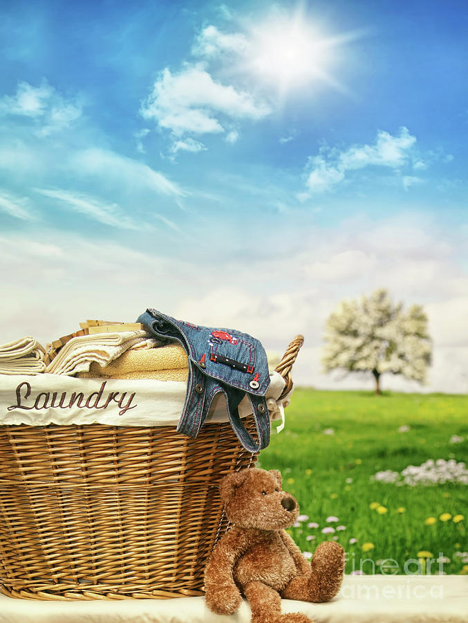 Laundry basket with clothes against a blue sky by Sandra Cunningham
