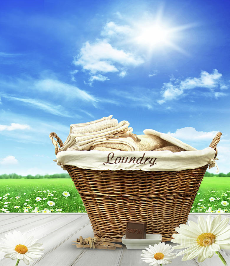 Laundry basket with clothes on rustic table against blue sky by Sandra Cunningham