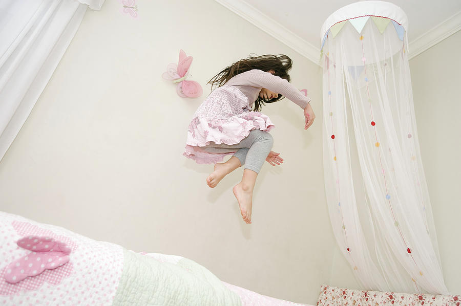 Child Photograph - Little Girl Dancing And Jumping On Her Bed by Bradley Hebdon