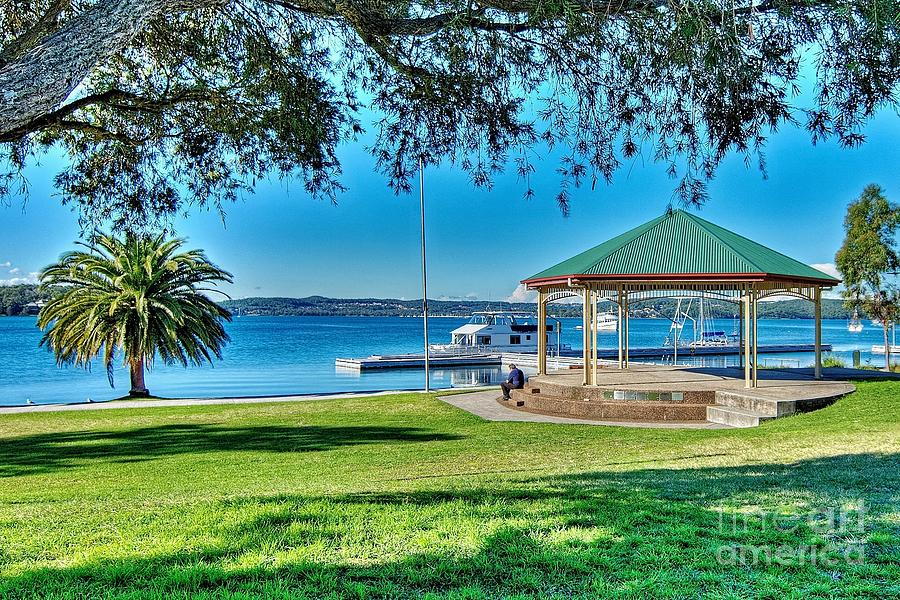 Lush green grassy waterfront park with a quaint little old Band by Geoff Childs