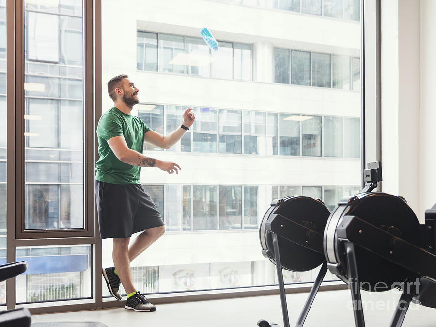 Man In A Gym Throwing A Bottle Up In The Air. Photograph ...
