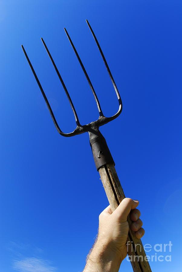 mans-hand-holding-up-pitchfork-against-b