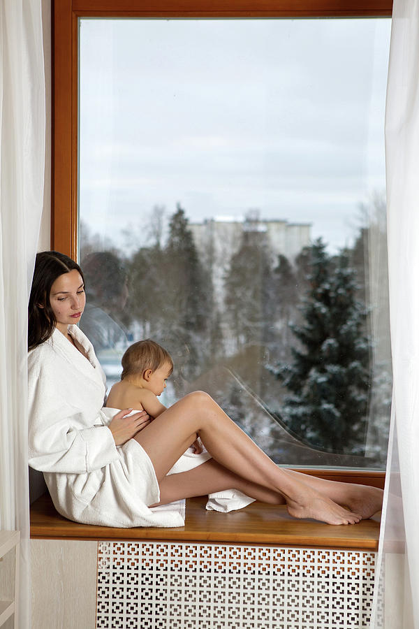Mom With Little Son Sits On The Window In A Bathrobe by Elena Saulich