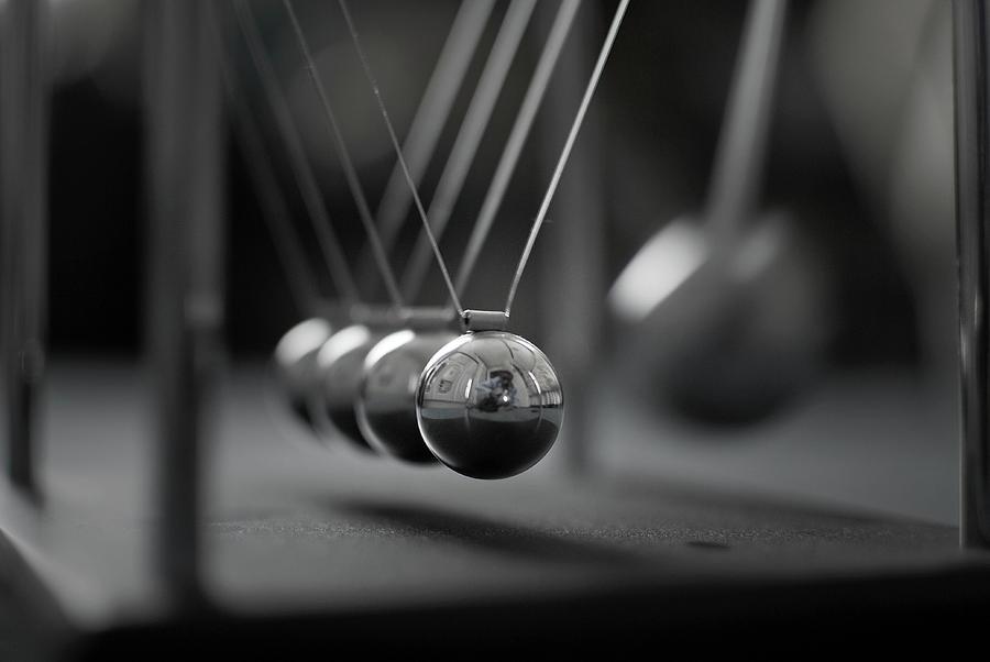 Horizontal Photograph - Newtons Cradle In Motion - Metallic Balls by N.J. Simrick