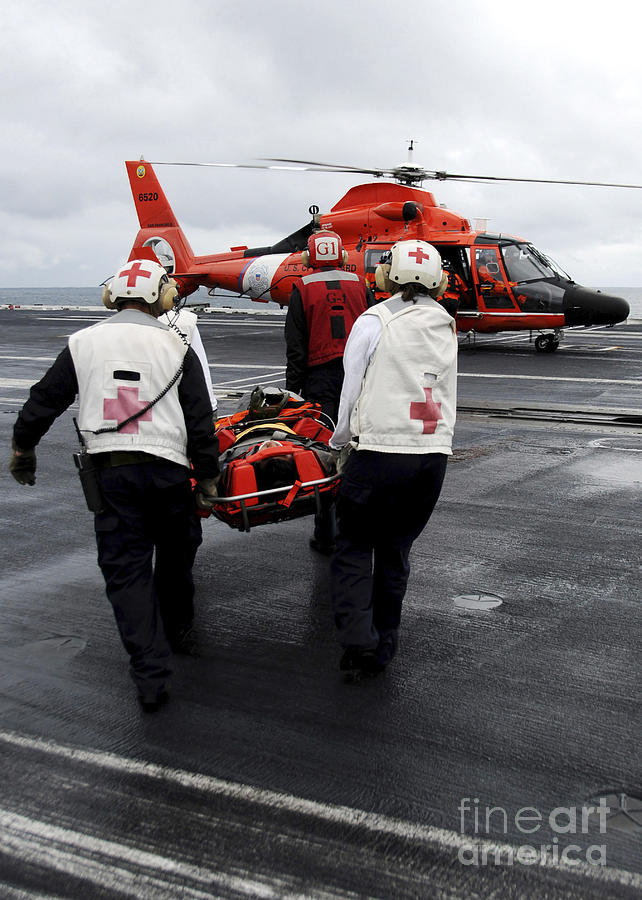 Coast Guard Photograph - Personnel Carry An Injured Sailor by Stocktrek Images