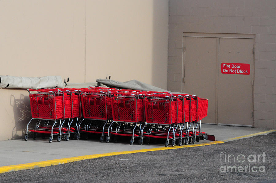 Shopping Carts Photograph - Red Shopping Carts in a row by Merrimon Crawford