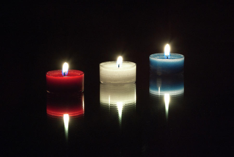 Red White And Blue Lighted Candles On A Black Reflective Mirror