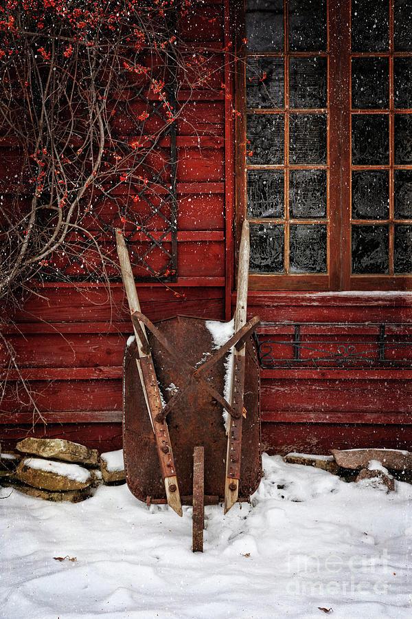 Atmosphere Photograph - Rusty Wheelbarrow Leaning Against Barn In Winter by Sandra Cunningham