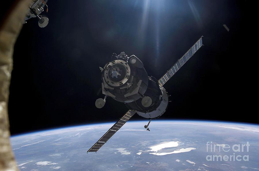 satellite orbiting around earth photograph by stocktrek images