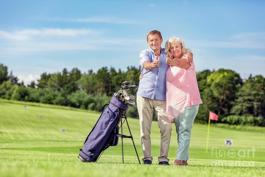 Senior Couple Giving Thumbs Up On A Golf Course. Photograph