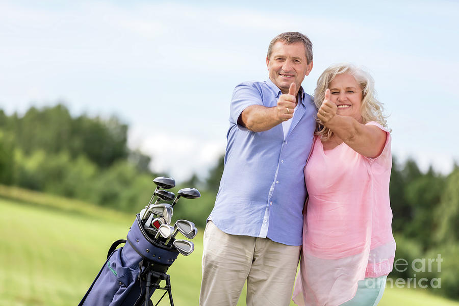Senior Couple Showing Ok Sign On A Golf Course. Photograph