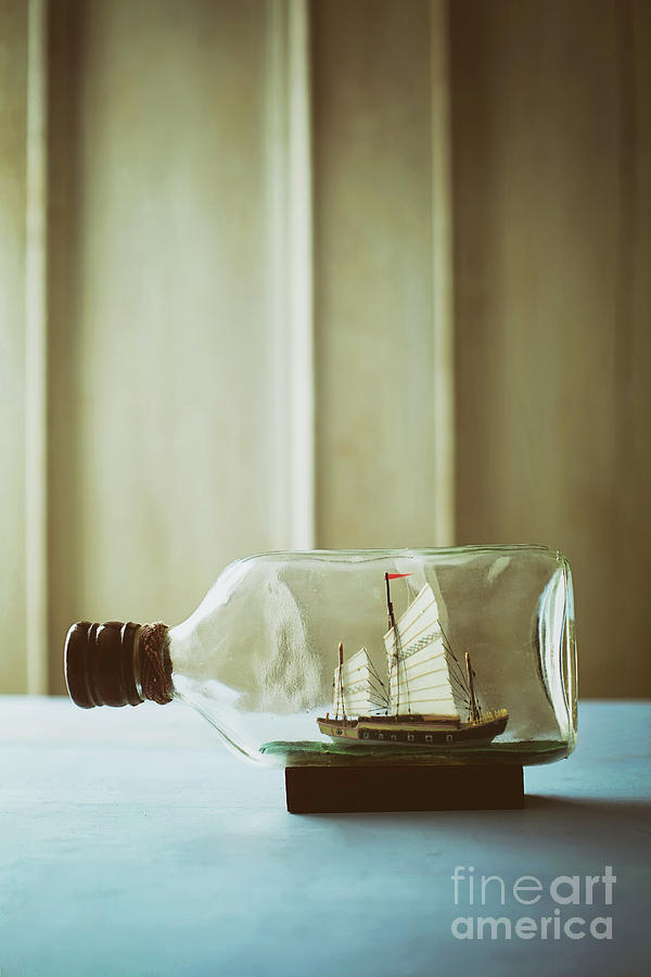 Small ship in a bottle on table by Sandra Cunningham
