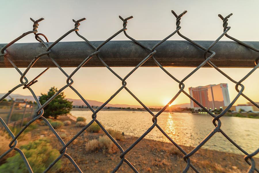 Summer Sunset Over Mgm Lake Looking Through A Fence With Grand Sierra Resort In The Background Photograph