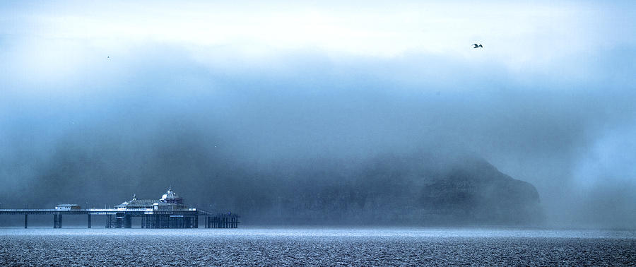 Pier Photograph - The Sea Mist Lifts To Reveal The Great Orme Behind Llandudno Pier by Mal Bray