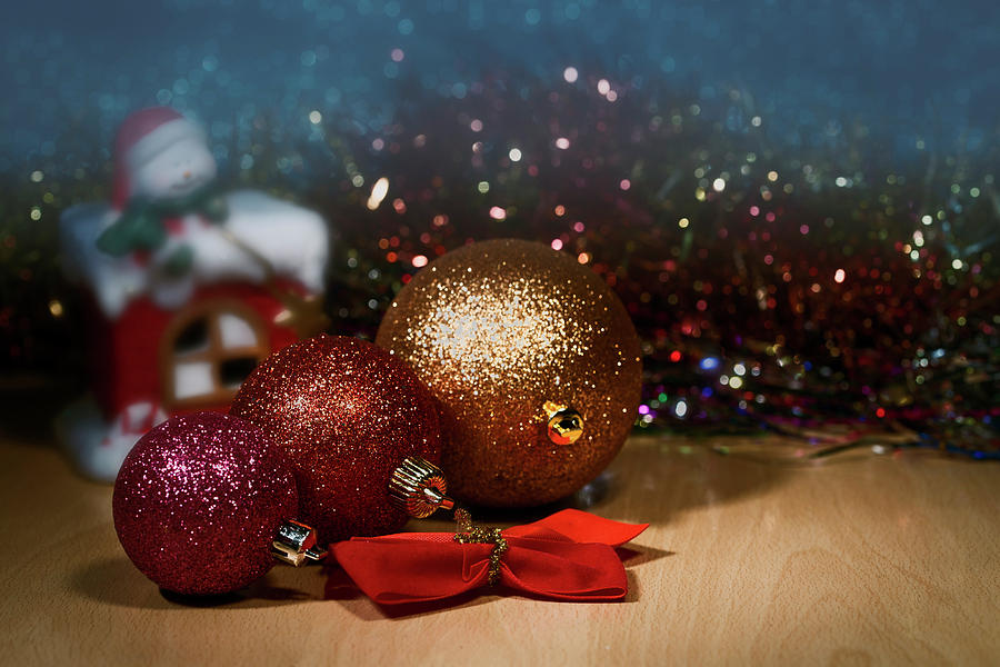 Colorful Christmas Balls.Three Colorful Christmas Ball On The Background Of Christmas Candlelight Snowman And Blurred Backgr