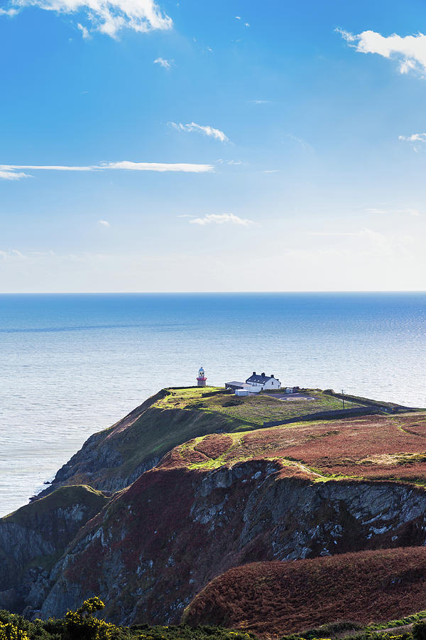 View of the trails on Howth Cliffs with the lighthouse in Irelan by Semmick Photo