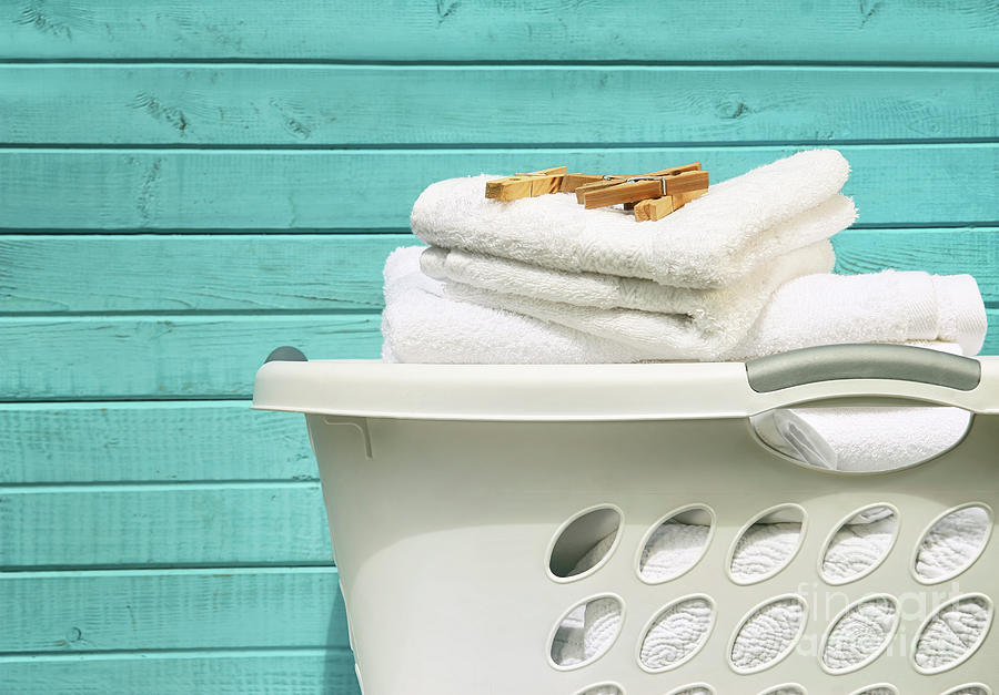 White laundry basket with towels and pins by Sandra Cunningham