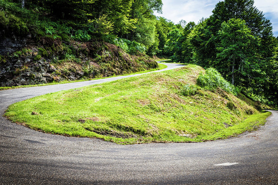 Winding road with sharp bend going up the mountain by Semmick Photo