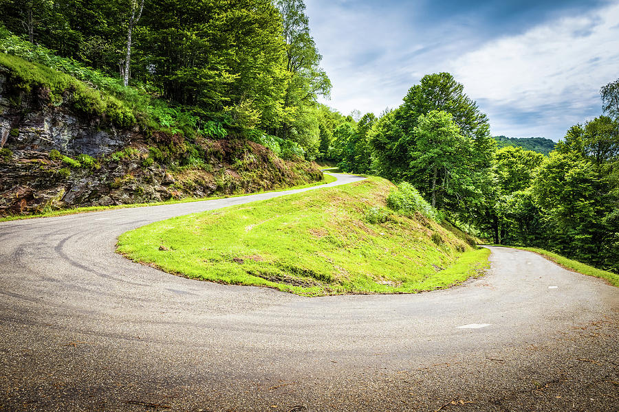 Winding road with sharp curve going up the mountain by Semmick Photo