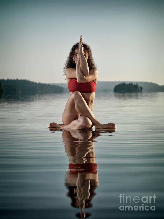 Woman Doing Sitting Variation Of Yoga Eagle Pose On The Water