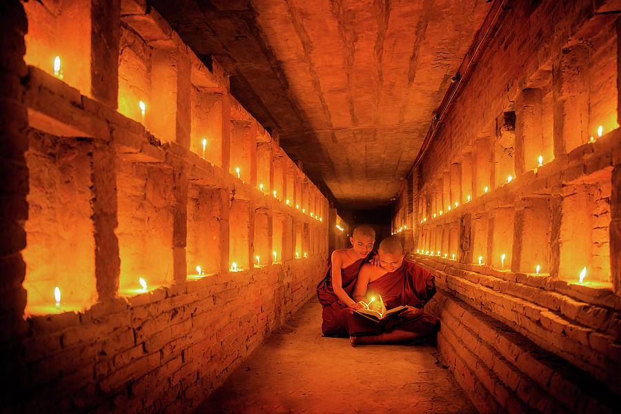 Alms Photograph - Young Buddhist Monk Are Reading A Book With Light From Candle  by Anek Suwannaphoom