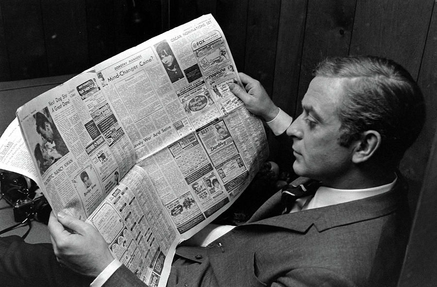 Actor Michael Caine Reading A Newspaper Photograph by Bill Ray