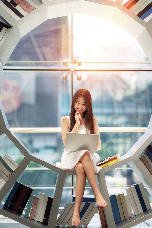 Asian girl student read a text book in library in her University by Anek Suwannaphoom