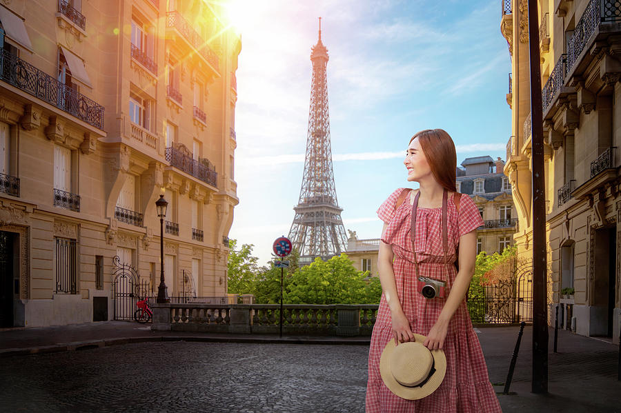 Asian girl walking in small paris street with view on the famous by Anek Suwannaphoom