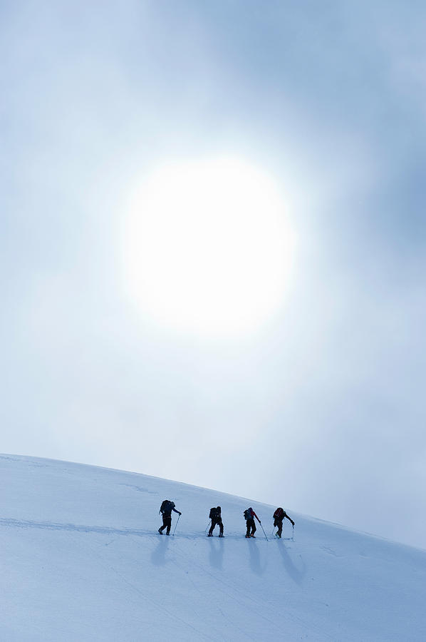 Backcountry Skiers Climbing Snowy Slope Photograph by Darryl Leniuk