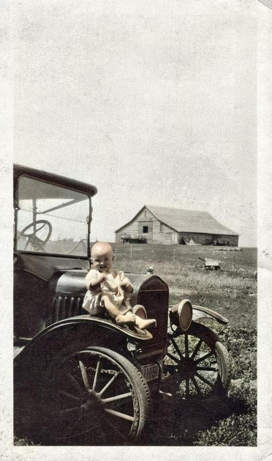 Bald Baby With Two Front Teeth The Baby Looks Pretty Happy Sitting On The Car Fender Of A Circa 1920 Painting