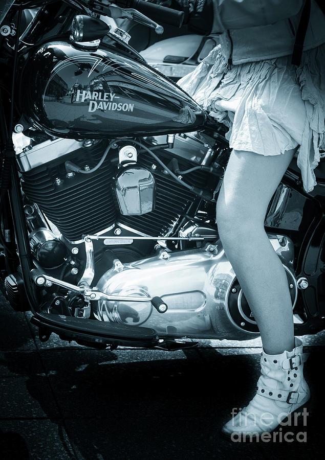 girl in short skirt astride Harley Davidson v twin black motorcy by Peter Noyce
