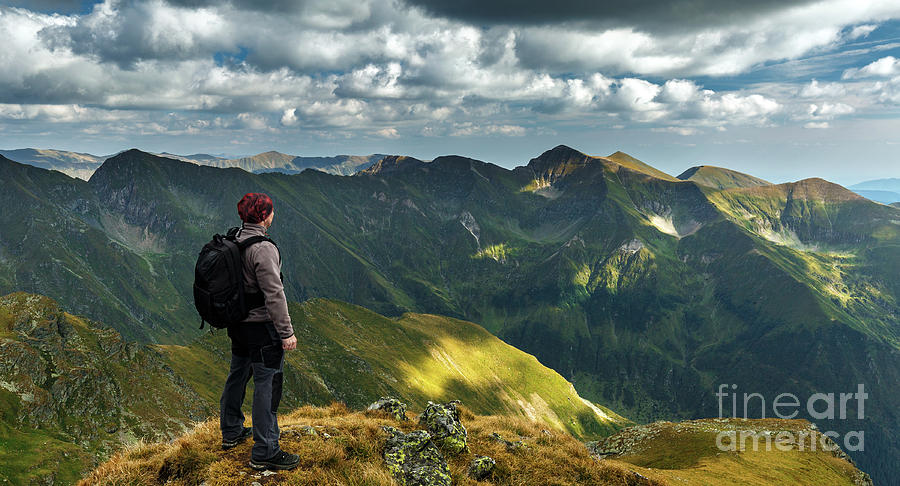 Hiker with backpack on mountains by Catalin Petolea