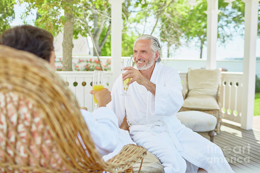 Bathrobe Photograph - Mature Couple In Spa Bathrobes Drinking Mimosas by Caia Image/science Photo Library