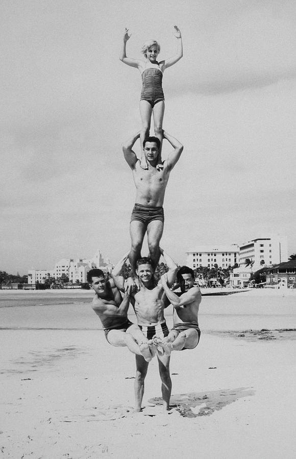 Men And Girl Perform Acrobatics On Beach Photograph by Archive Holdings Inc.